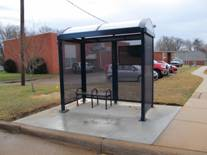Bus Stop shelter with transparent walls and a two seat bench